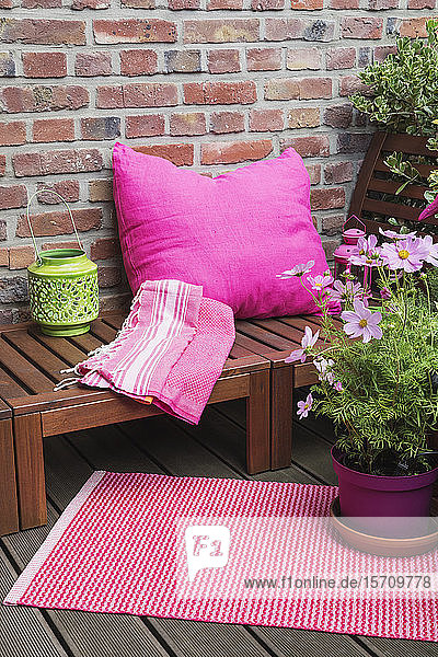 Balcony with bench  pink cushion  blanket  lantern  mat and various potted plants