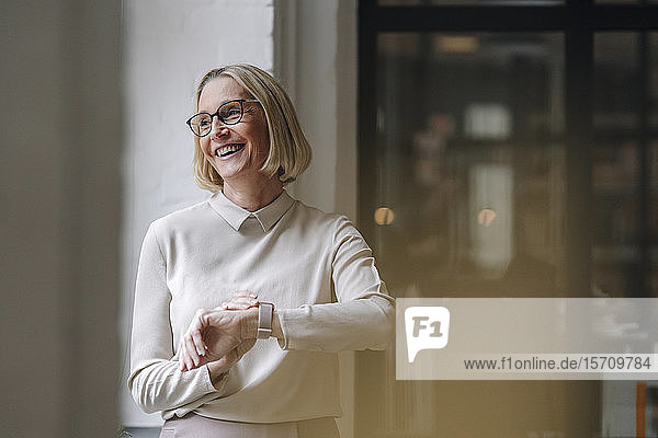 Happy mature businesswoman at the window in office