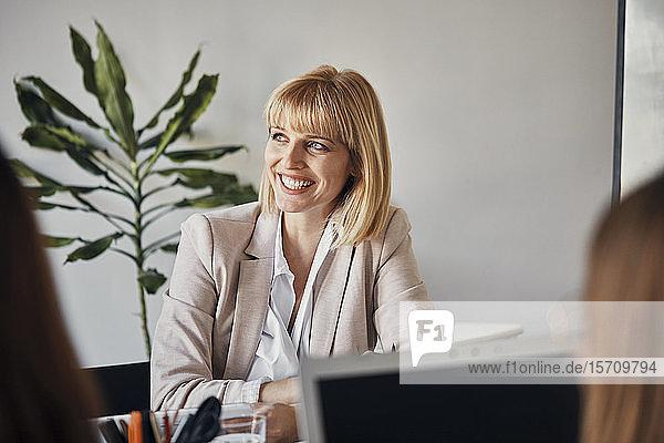 Porträt einer lächelnden Geschäftsfrau während einer Besprechung im Büro