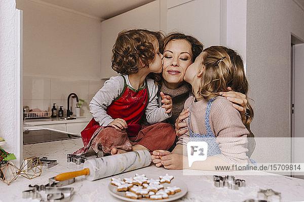 Mädchen küssen Mutter in der Küche mit Weihnachtsplätzchen auf der Theke