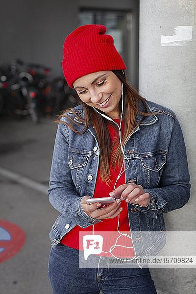 Frau mit rotem Pullover und Wollmütze  die sich vor einer Wand ein Selfie nimmt