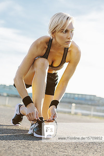 Blonde woman jogging  tying shoes