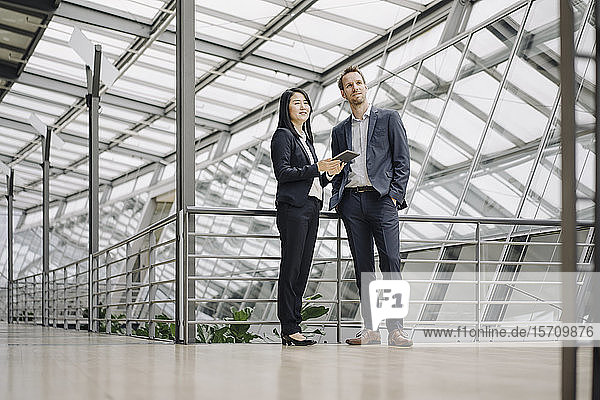 Businessman and businesswoman with tablet standing in modern office building