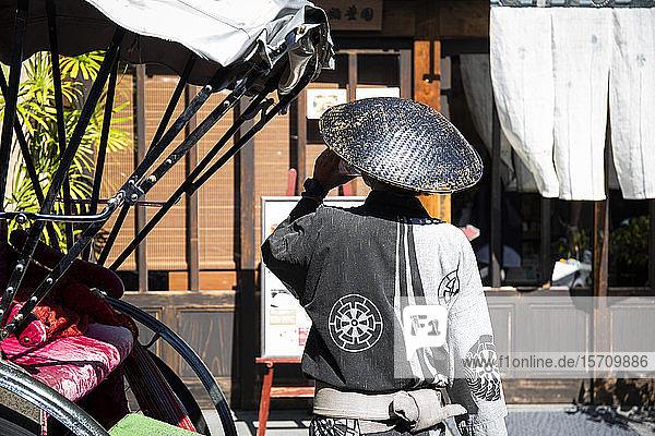 Japan  Takayama  Rear view of jinrikisha driver drinking water