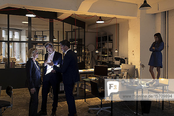 Business people discussing at shining tablet in office with girl standing on desk besides