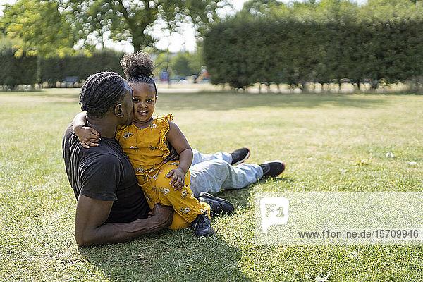 Liebender Vater und Tochter entspannen sich auf einer Wiese in einem Park Liebender Vater und Tochter entspannen sich auf einer Wiese in einem Park
