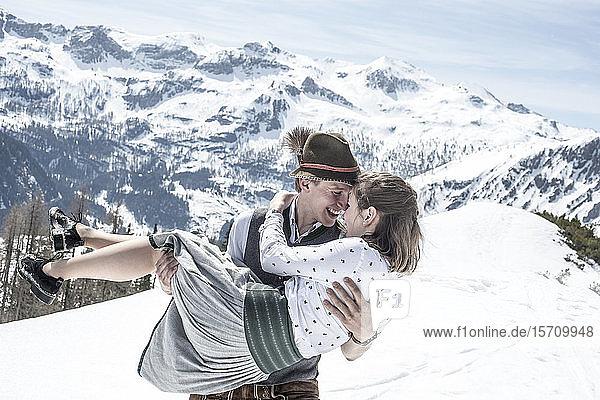 Glückliches Paar küsst sich in den verschneiten Bergen  Bundesland Salzburg  Österreich