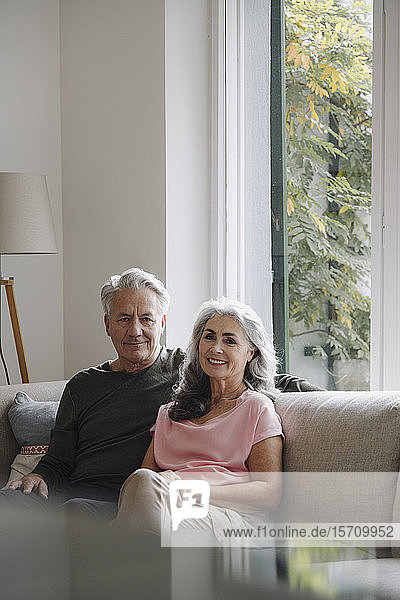 Portrait of senior couple relaxing on couch at home