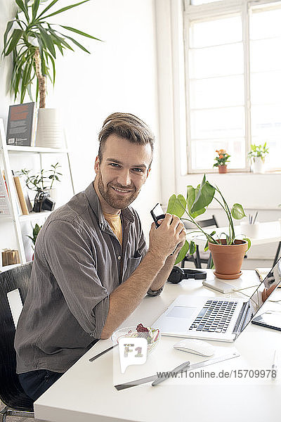 Portrait of smiling man with smartphone having lunch break at desk in office