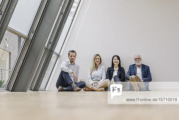 Porträt von lächelnden Geschäftsleuten  die im Büro auf dem Boden sitzen