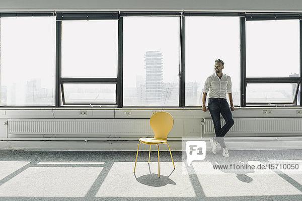 Ein reifer Geschäftsmann steht am Fenster in einem leeren Büro
