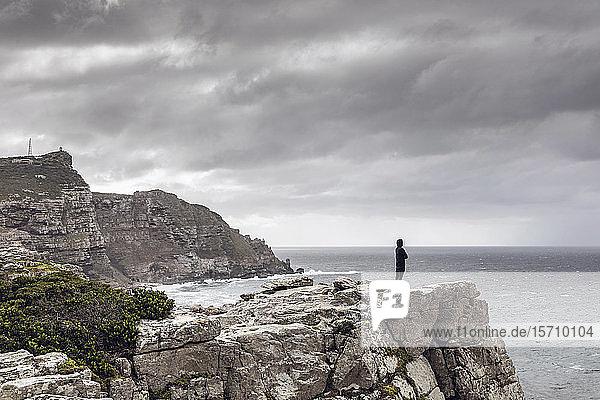 Mann steht auf felsiger Klippe und schaut zum Horizont  Cape Point  Westkap  Südafrika