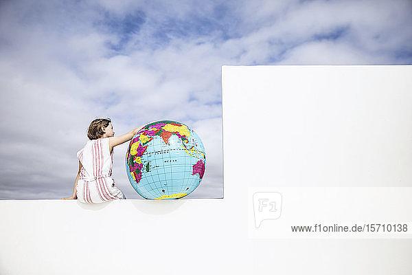 Kleines Mädchen an der Wand sitzend  mit Arm um den aufblasbaren Globus  Rückansicht