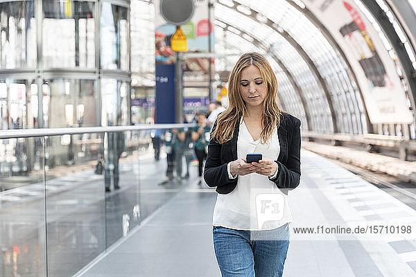 Frau mit Smartphone auf dem Bahnsteig  Berlin  Deutschland
