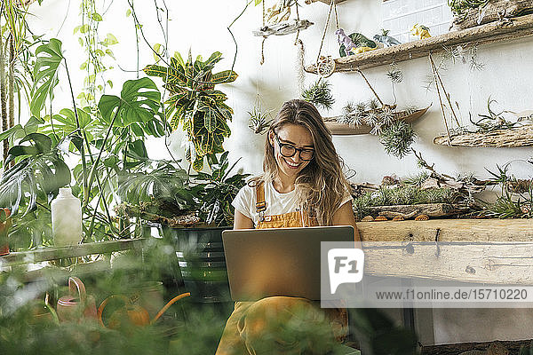 Happy young woman using laptop in a small gardening shop