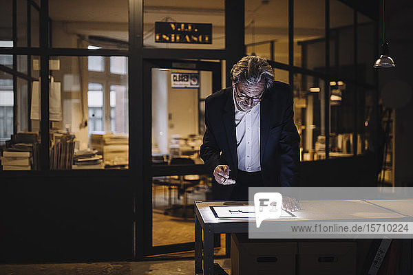 Senior businessman looking at shining tablet in office