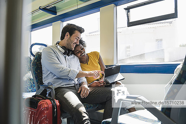 Happy young couple using tablet in a train
