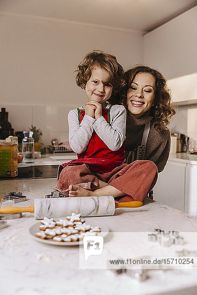 Portrait of happy mother and daughter with Christmas cookies in kitchen