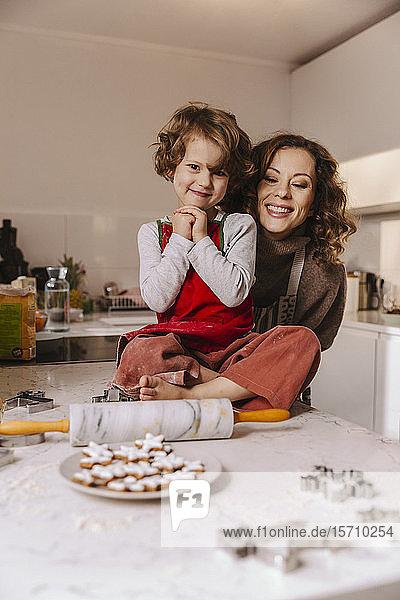 Porträt einer glücklichen Mutter und Tochter mit Weihnachtsplätzchen in der Küche