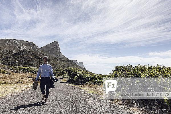 Barfüßiger Geschäftsmann auf Landstraße  Cape Point  Westkap  Südafrika