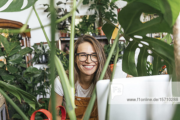 Portraitof a happy young woman with laptop surrounded by plants