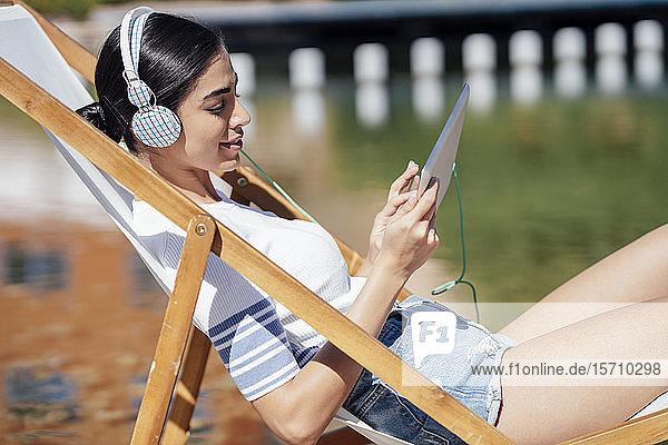 Junge Frau sitzt in einem Liegestuhl  trägt Kopfhörer und benutzt ein Tablett