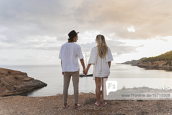 Back view of young couple in love standing in front of the sea  Ibiza  Balearic Islands  Spain