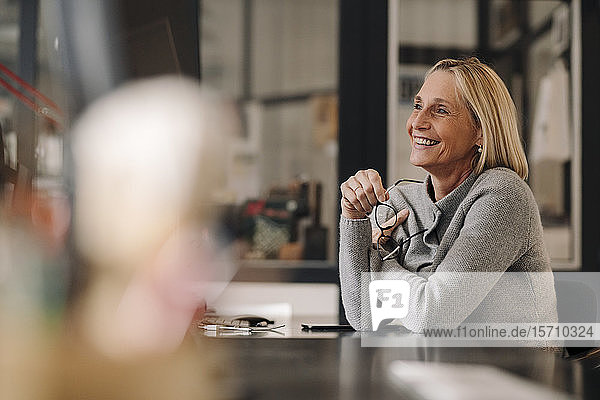 Happy mature businesswoman sitting at desk in office