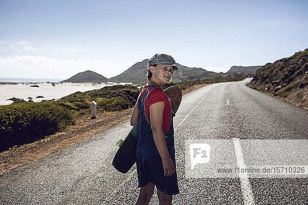 Porträt eines lächelnden Mädchens mit Skateboard auf der Landstraße stehend  Kapstadt  Western Cape  Südafrika
