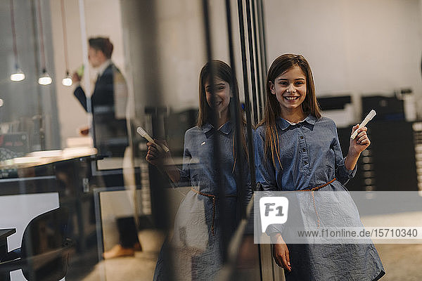 Happy girl drawing on glass pane in office