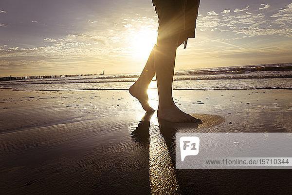 Niederlande  Cadzand-Bad  Beine eines Teenagers  der in der Dämmerung am Strand spazieren geht