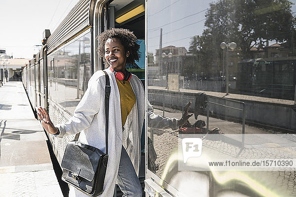 Smiling young woman entering a train