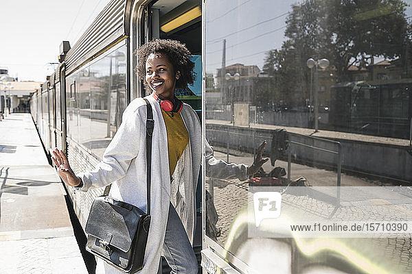 Lächelnde junge Frau beim Einsteigen in einen Zug