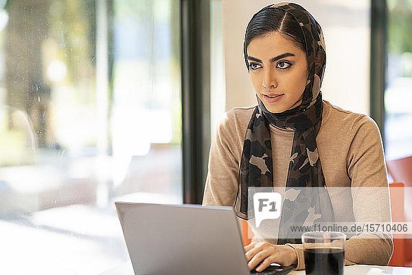 Junge Frau trägt Kopftuch mit Laptop in einem Café