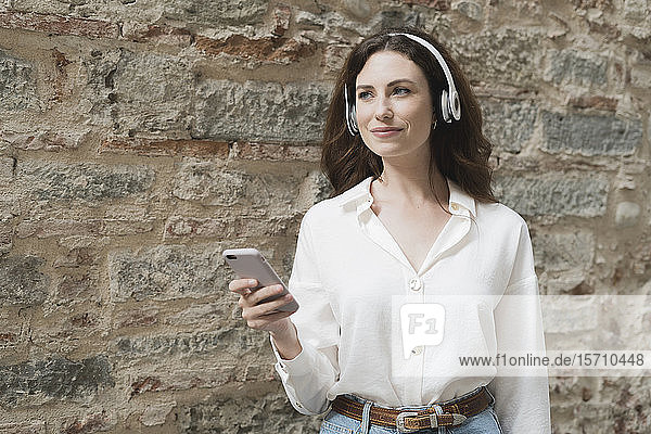 Young woman with smartphone and headphones outdoors at a stone wall