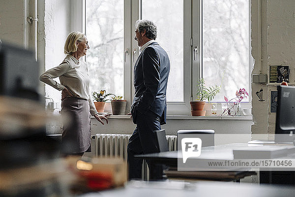 Smiling businessman and businesswoman talking at the window in office