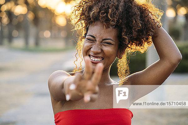 Junge glückliche Frau drückt V-Geste mit den Fingern aus