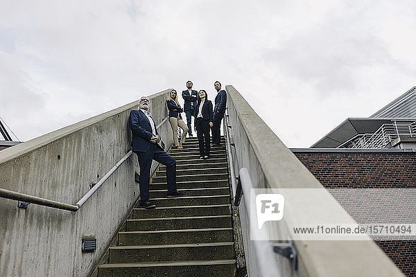Business people standing on exterior stair looking out
