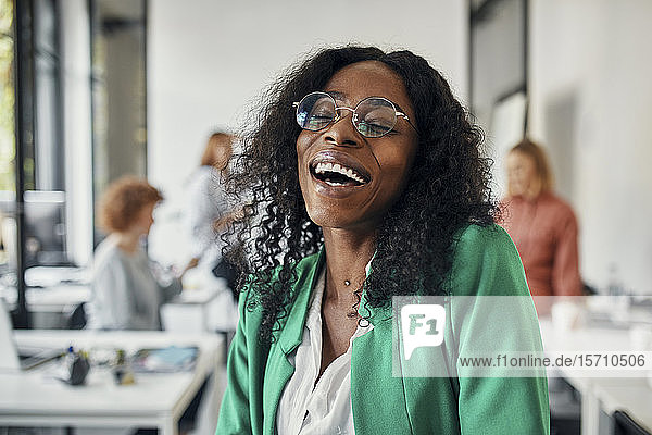 Portrait of a laughing businesswoman in office with colleagues in background