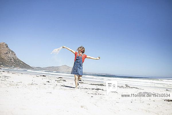 Mädchen hört Musik mit Kopfhörern  tanzt am Strand  Kapstadt  Western Cape  Südafrika