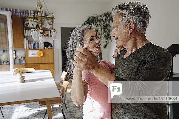 Senior couple dancing in living room at home