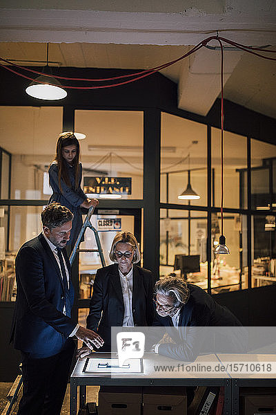 Business people discussing at shining tablet in office with girl on ladder standing besides
