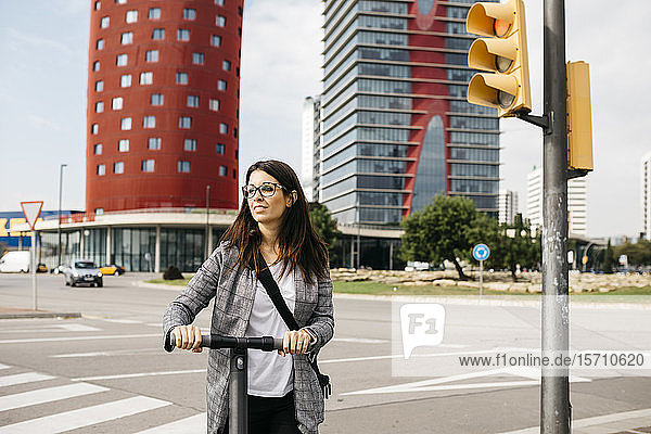 Young businesswoman with e-scooter in the city