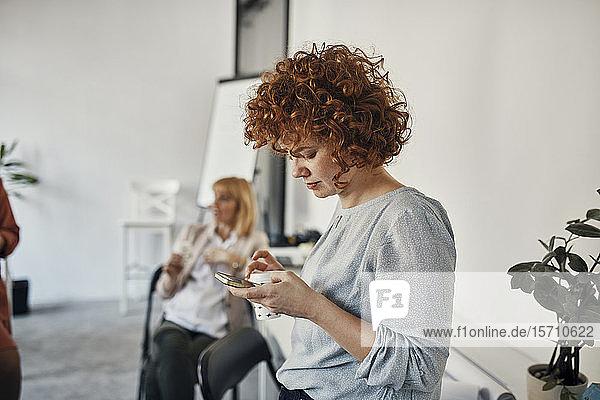 Businesswoman having a break in office using smartphone