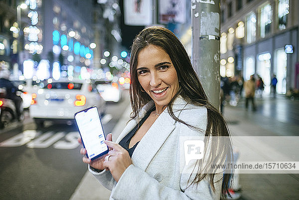 Happy woman showing her smartphone in the street at night