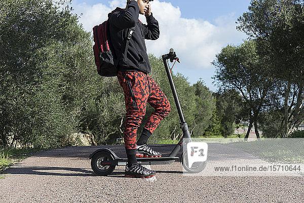 Junger Mann mit E-Scooter auf dem Fahrradweg