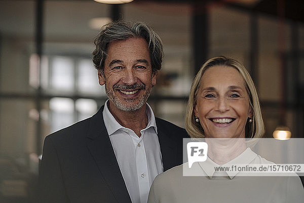 Portait of smiling businessman and businesswoman in office