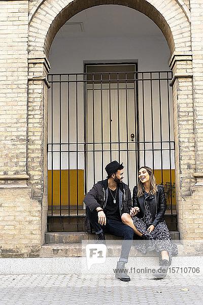 Lachendes junges Paar sitzt auf einer Treppe im Freien