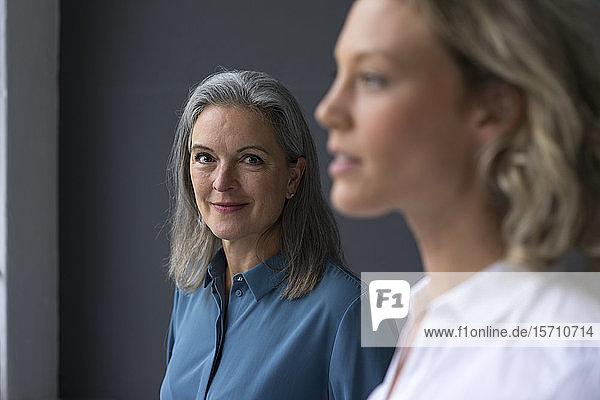 Porträt einer selbstbewussten reifen Geschäftsfrau mit einer jungen Geschäftsfrau im Vordergrund