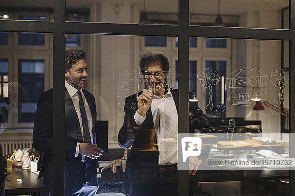 Two businessmen working on drawing on glass pane in office